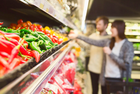 Chili peppers arranged in shelf with couple shopping in background at supermarketの写真素材 [FYI02138346]