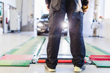 Low section of mechanic standing in front of car coming towards hydraulic liftの写真素材 [FYI02138381]