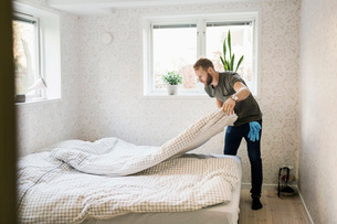Full length of man making bed in houseの写真素材 [FYI02138383]