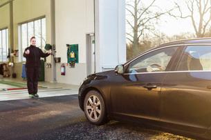 Female mechanic guiding man to drive car into auto repair shopの写真素材 [FYI02138391]