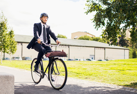 Full length of businessman riding bicycle on street against skyの写真素材 [FYI02138400]