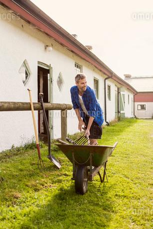 Smiling farmer removing equipment from wheelbarrow at farmの写真素材 [FYI02138412]