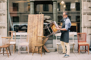 Full length of man holding chair while arranging outside storeの写真素材 [FYI02138476]