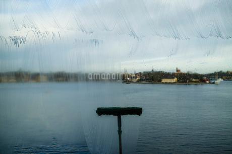 Window washer cleaning glass wall against seaの写真素材 [FYI02138625]