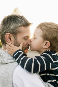 Close-up of son kissing father's nose against clear skyの写真素材 [FYI02138631]