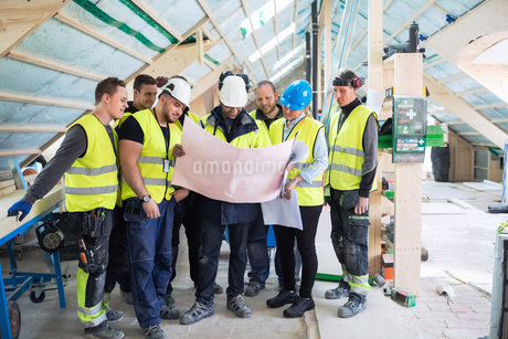 Manager standing with manual workers while reading blue prints at construction siteの写真素材 [FYI02138689]