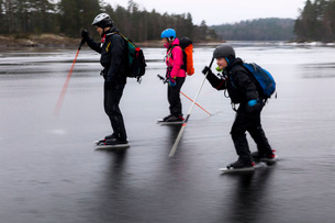 Father and children ice-skating on frozen lakeの写真素材 [FYI02138717]