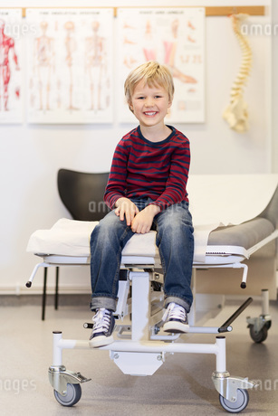 Portrait of happy boy sitting on examination table in orthopedic clinicの写真素材 [FYI02138761]
