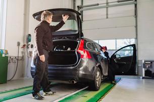 Full length of mechanic closing car trunk in auto repair shopの写真素材 [FYI02138783]