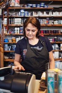 Woman using cash register in shoe repair shopの写真素材 [FYI02138866]