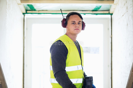 Portrait of serious man wearing ear protectors standing against windowの写真素材 [FYI02138961]
