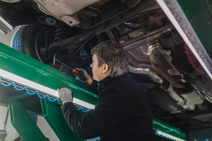 Side view of male mechanic examining car with hammer in auto repair shopの写真素材 [FYI02138976]