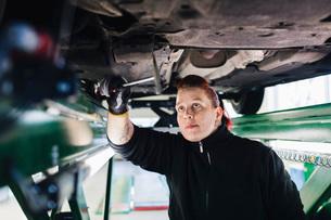 Female mechanic examining car with hammer in auto repair shopの写真素材 [FYI02138986]