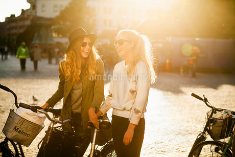 Happy friends with bicycles enjoying on city streetの写真素材 [FYI02139009]