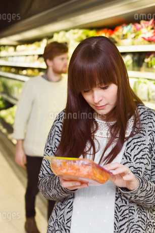 Young woman reading label on product at supermarketの写真素材 [FYI02139076]
