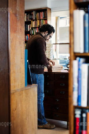 Man reading book while standing seen from shelvesの写真素材 [FYI02139100]