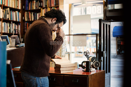Owner holding eyeglasses while reading book in libraryの写真素材 [FYI02139167]