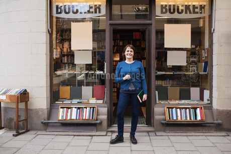 Portrait of happy woman holding book while standing outside bookstoreの写真素材 [FYI02139209]
