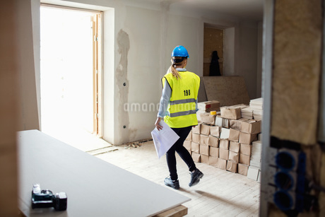 Female manual worker looking at stack of boxes while walking at siteの写真素材 [FYI02139244]