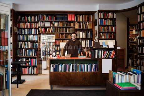 Portrait of owner standing against bookshelves in libraryの写真素材 [FYI02139245]