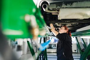 Side view of female mechanic repairing car on hydraulic liftの写真素材 [FYI02139258]