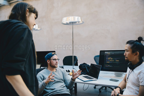 Computer programmer gesturing while discussing plan with colleagues in creative officeの写真素材 [FYI02139259]