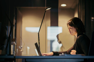 Side view of businesswoman using laptop at desk in dark officeの写真素材 [FYI02139265]