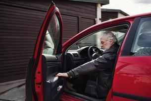 Senior man sitting in red car and closing door against garageの写真素材 [FYI02139266]