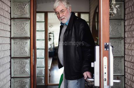 Senior man wearing leather jacket closing doorの写真素材 [FYI02139270]