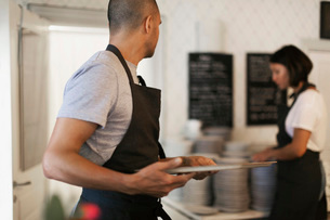 Man holding serving tray looking at female colleague standing by stack of plates in cafeの写真素材 [FYI02139287]