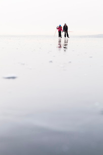 Father and daughter ice-skating on frozen lakeの写真素材 [FYI02139315]