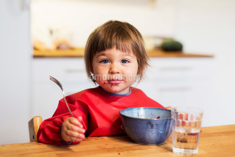 Portrait of little girl with messy mouth eating fruit salad at homeの写真素材 [FYI02139331]
