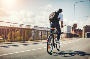 Rear view of businessman riding bicycle on bridge in cityの写真素材 [FYI02139340]