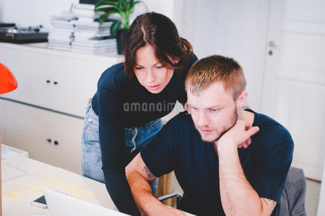 Business colleagues using laptop at desk in creative officeの写真素材 [FYI02139355]
