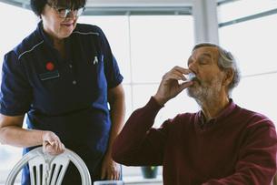Caretaker looking at senior man taking medicineの写真素材 [FYI02139386]
