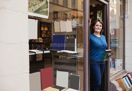 Portrait of smiling librarian holding book while standing at doorwayの写真素材 [FYI02139392]