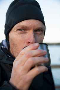 Male hiker drinking coffee outdoorsの写真素材 [FYI02139429]