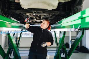 Female mechanic examining car with hammer in auto repair shopの写真素材 [FYI02139451]