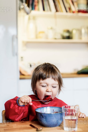Little girl eating fruit salad at table in houseの写真素材 [FYI02139458]
