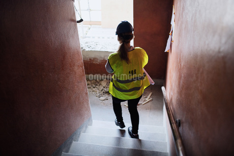 Rear view of female manual worker walking steps at construction siteの写真素材 [FYI02139522]