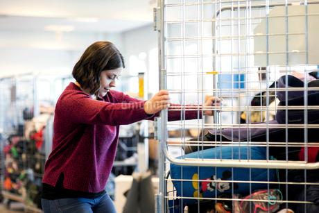 Side view of woman closing metallic gate at workshopの写真素材 [FYI02139536]