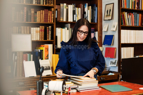 Female librarian looking at books in bookstoreの写真素材 [FYI02139558]