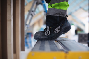 Low section of man wearing shoes standing on ladderの写真素材 [FYI02139597]