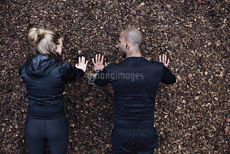 Directly above shot of couple doing plank exercise in forestの写真素材 [FYI02139637]