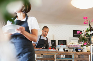 Woman holding plate and walking against male colleague working at cafe counterの写真素材 [FYI02139645]