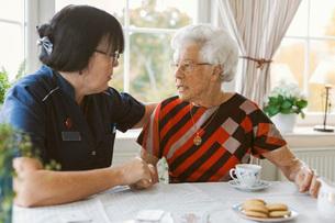 Female caretaker consoling senior woman at nursing homeの写真素材 [FYI02139659]