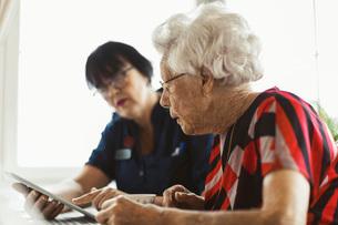 Senior woman using digital tablet with caretaker at homeの写真素材 [FYI02139662]
