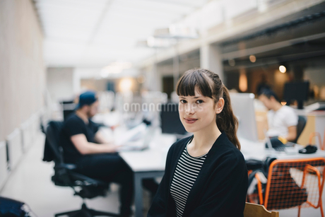 Portrait of confident computer programmer at office with colleagues working in backgroundの写真素材 [FYI02139670]