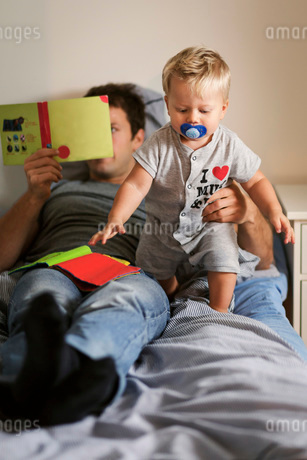 Father reading book while holding baby in bedの写真素材 [FYI02139674]