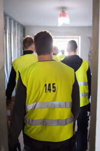 Rear view of manual workers walking in corridor at construction siteの写真素材 [FYI02139681]